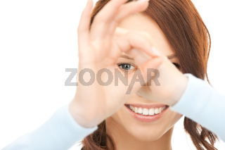 lovely woman looking through hole from fingers