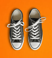 Black sneakers isolated on orange background