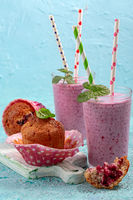 Homemade muffins with black currant and berry milkshake.