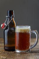 hausgemachtes dunkles Bier auf Holz