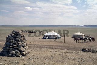 Jurten und Tiere mongolischer Araten in der Wüste Gobi, im Vordergrund ein Owoo, Foto von 1977