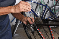 Bike maintenance. Closeup of a technicians hands using a screwdriver to make fine adjustments to a Bicycle derailleur.