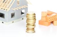 Finanzierungssymbol mit Rohbau und Geldmünzen