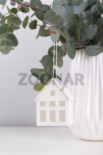 Bouquet of eucalyptus in the ceramic vase and small decorative house on the table against grey wall