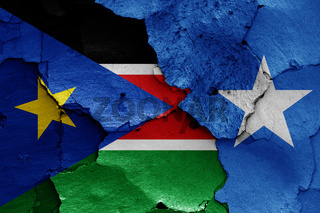 flags of South Sudan and Somalia painted on cracked wall