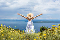 Rear view of young woman wearing striped summer dress and straw hat standing in super bloom of wildflowers, relaxing with hands up to the sky, enjoing beautiful view of Adriatic sea nature, Croatia
