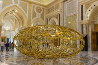 The Power of Words is a golden sculpture featuring interlaced Arabic words
