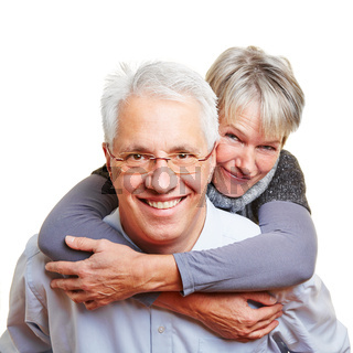 Mann trägt Seniorin huckepack auf dem Rücken