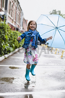 Cheerful small girl having fun in puddle on street