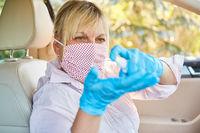 Putzkraft trägt Desinfektionsmittel auf in Mietwagen wegen Coronavirus