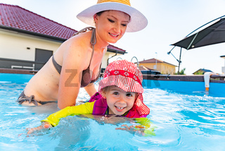 2-3 years old child with mother in swimming pool learn to swim. Summer at home concept.