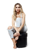 Young pretty in jeans and shirt woman sitting on pouffe stool