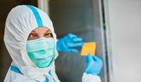 Mitarbeiter bringt gelbe Klebenotiz oder Zettel an Tür von Klinik an