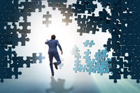 Businessman breaking the wall of jigsaw puzzle