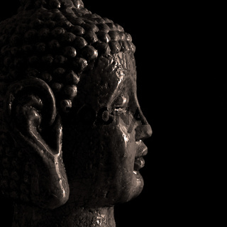 Buddha statue close up on a black background
