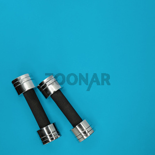 Metal small dumbbells on a blue background.