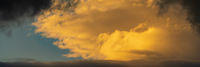 Panorama dramatic clouds illuminated rising of sun floating in blue sky. Natural weather, meteorology background
