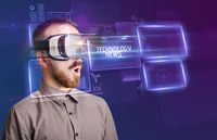 Businessman looking through Virtual Reality glasses, tech concept