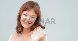 Mature brown-haired female applies skin care cream by touching face with hand, close up. Woman applying anti-age cream on her skin isolated on white background. Spa and wellness concept