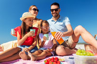 happy family having picnic on summer beach