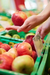Hand hält Apfel im Supermarkt