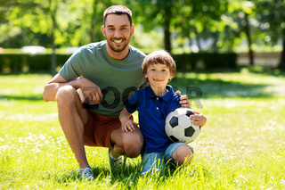 father and little son with soccer ball at park
