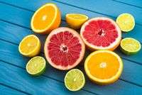 bright and juicy oranges, grapefruits, limes and lemons lie on a blue wooden table