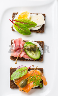 Variation of healthy open sandwiches on Pumpernickel bread with vegetables