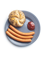 Fresh frankfurter sausages with bun and ketchup on plate