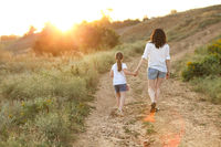 Loving mother walking with daughter in countryside