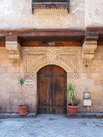 Stone bricks wall with arched wooden door of house of Moustafa Gaafar Al Selehdar, Cairo, Egypt
