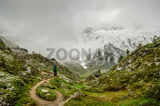 Hiking man at a green grassy mountain with the view through the fog at a high snow covered mountain.