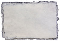 isolated stack of gray toned deckle edge paper sheets