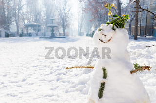 Snowman with fountain and advent stalls of Zrinjevac Park in Zagreb in winter with snow and sunshine, Croatia, Europe
