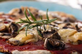 Rosmarin auf einer Pilzpizza auf einem Teller