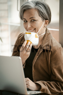 White-haired woman in age smiles taking off her mask and looking at the camera. Smiling woman with protective mask works laptop sitting on sill. Tinted image