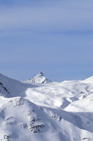 Snowy off-piste slope, sunlit plateau and peak at high winter mountains