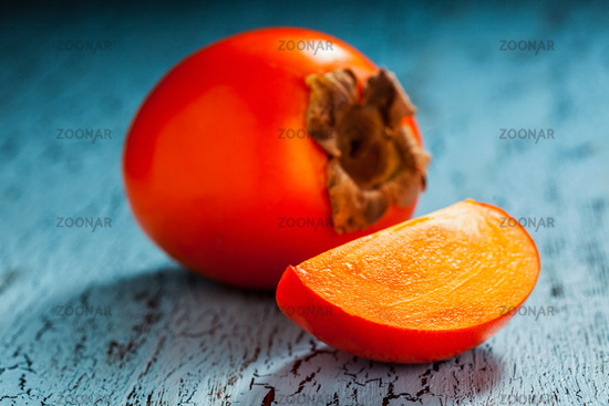 Fresh ripe persimmon with slice on a blue wooden background