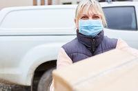 Paketbotin mit Mundschutz draußen liefert Paket aus