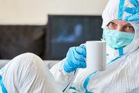 Pflegepersonal in Klinik in Schutzkleidung ist erschöpft und macht Pause mit Tasse