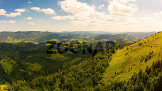 Aerial drone view of picturesque nature with green coniferous forests on the slopes of the mountains in beautiful sunny day