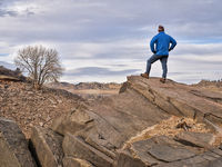 male hiker on a rocky cliff  at foothills of Rocky Mountains