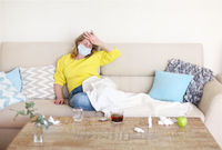 Sick woman with fever on sofa
