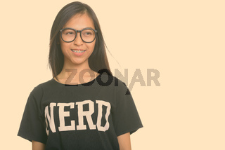 Studio shot of young happy Asian teenage nerd girl smiling while thinking