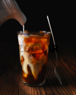 Closeup of a glass of iced coffee on a dark wood table. Fresh pouring cream is permeating through the glass
