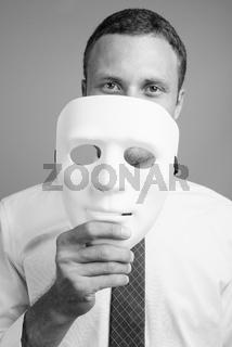 Portrait of handsome businessman against gray background