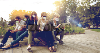 teenage students in masks with computers at campus