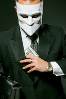 Unrecognizable businessman in a white mask hides or takes money from his breast pocket. Masked caucasian man holding banknote. Close up portrait. Corruption and bribery concept. Toned image