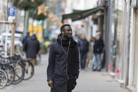 Young Black Man with Earphones Standing on Sidewalk with Head Turned