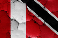 flags of Peru and Trinidad and Tobago painted on cracked wall